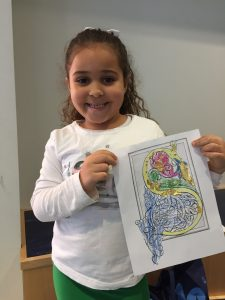 "A young patron proudly holds up a coloring page with an ""S"" shaped dragon she has colored yellow and foliage that she has colored pink, green, and blue. Gold glitter adorns the fire that the dragon is breathing and is visible along the dragon's neck as well."