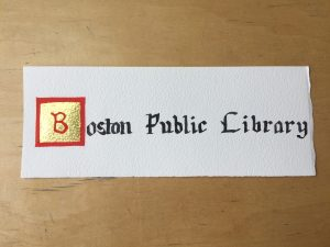 "A piece of paper with ""Boston Public Library"" calligraphed on it sits on a wooden background. The ""B"" of Boston is written in red and is on a golden background which is bordered in red. The rest of the letters are in black."