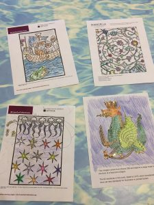 "Four more examples of ""gilt"" coloring pages are visible sitting on a table's surface. The upper left hand corner illustration is of a boat from which a man is falling into water where a dragon lurks. The upper right hand coloring page is of swirling foliage. The lower left hand corner coloring page is of stars falling from a field of swirling clouds. The lower right hand coloring page is of a cannon that was made to look like a crowned dragon. All of these pages are brightly colored and covered with gold glitter."