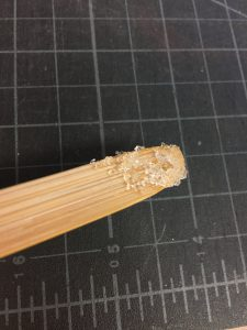 Clear cooked gelatin in tiny globules clings to the surface of a bamboo spatula in front of a black cutting mat background.