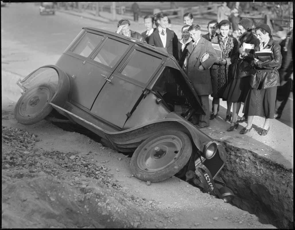 crashed car with onlooking crowd
