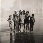A group of kids standing in a wet street, soaked, during the summer.