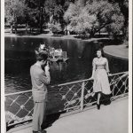 A man taking a photograph of a woman on the walkway above the water in the Boston Public Garden. ca. 1935–1955]