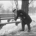A man reaches out to touch a squirrel on a bench in the Boston Common in winter