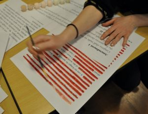 Photo of a person removing parts of a test to create an erasure poem