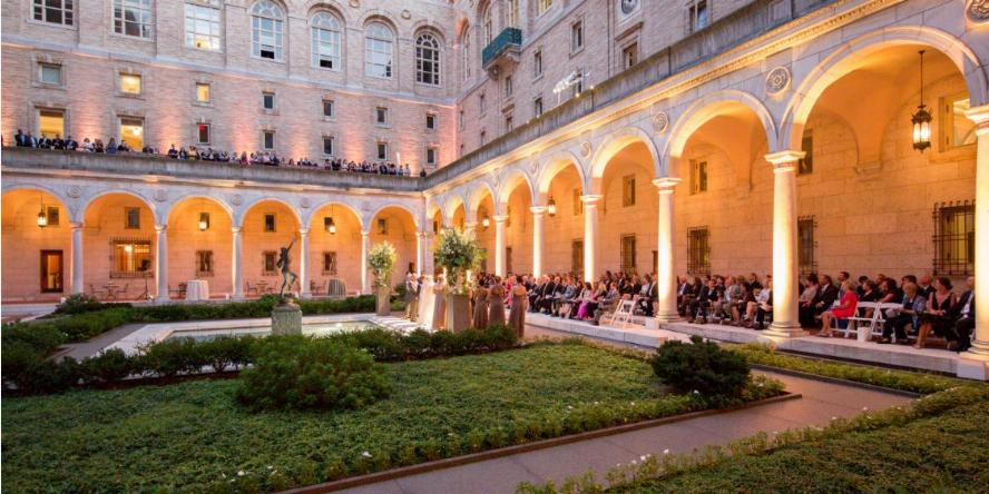 Guests are gathered behind the pillars in seats in the courtyard, while a group of people, including the bride and groom, stand in the courtyard, facing the guests