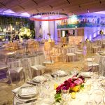 Boylston Hall set up with circular tables, white tablecloths, and white chairs. The chairs have a clear back, and there are centerpieces of each table. The hall is lit with blue lighting.