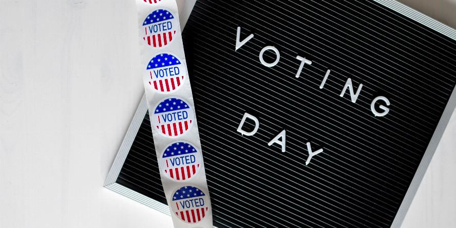 """A sign that says """"Voting Day"""" with a roll of """"I Voted"""" stickers unfurling over the sign with a white background"""