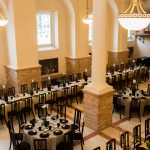 The Guastavino set up with circular tables in the middle, and long rectangular tables on the sides. Both types of tables are set up with chairs, tablecloths, plates, napkins, utensils and flowers