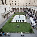 Birds eye view of an event in the McKim Courtyard. There is a band playing off to the side of the fountain, and chairs set up for guests opposite the fountain.