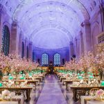 Long view of Bates hall decorated with white and gold tablecloths on the tables, with individual flower arrangements at each seat, as well as large pink flower arrangements at each table