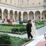 Photo of a bride being walked down the aisle in the McKim courtyard. Opposite her there are guests seated. In front of them is the groom, who is also facing the fountain.