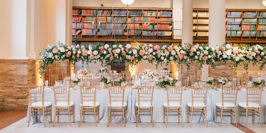 Guastavino Room set up with long tables. Each table has a white tablecloth, and place settings. There are gold backed chairs with white cushions. There are small medium, and large flower arrangements on the tables. The colors of the flowers are white, pink, and peach. It looks like it is set up for a wedding reception.