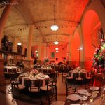 Photo of the Guastavino Room set up with tables and chairs, tablecloths, plates, utensils, and flower arrangements. There is also red lighting.