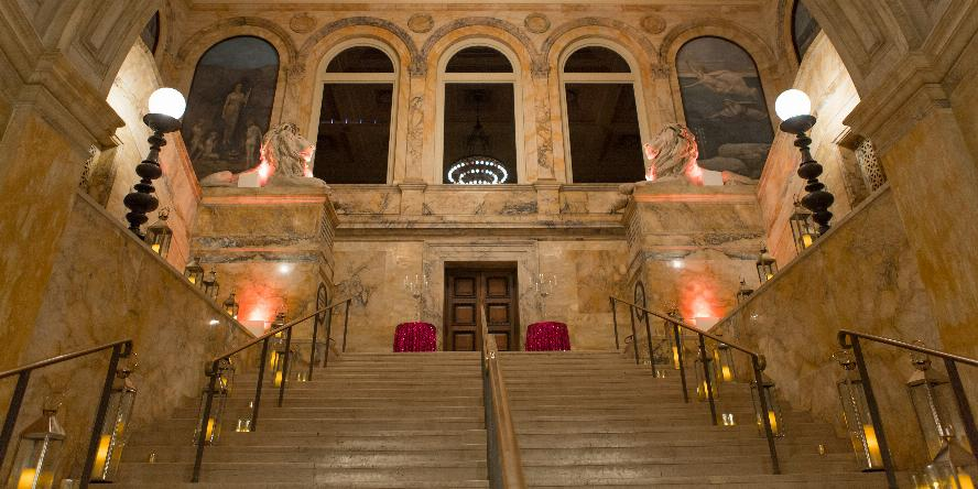 Photo of the Grand Staircase in the McKim Lobby. On the sides of the staircase, outside of the rails, there are large glass lanterns with candles inside. At the top of the stairs are two circular tables with red tablecloths. Further above you can see the marble lions on either side of the staircase. On the ceiling the chandelier is lit.