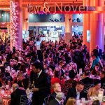 Photo of Boylston Hall with people seated at tables for the 2019 BPL Gala. There is a large flower stand with peonies.