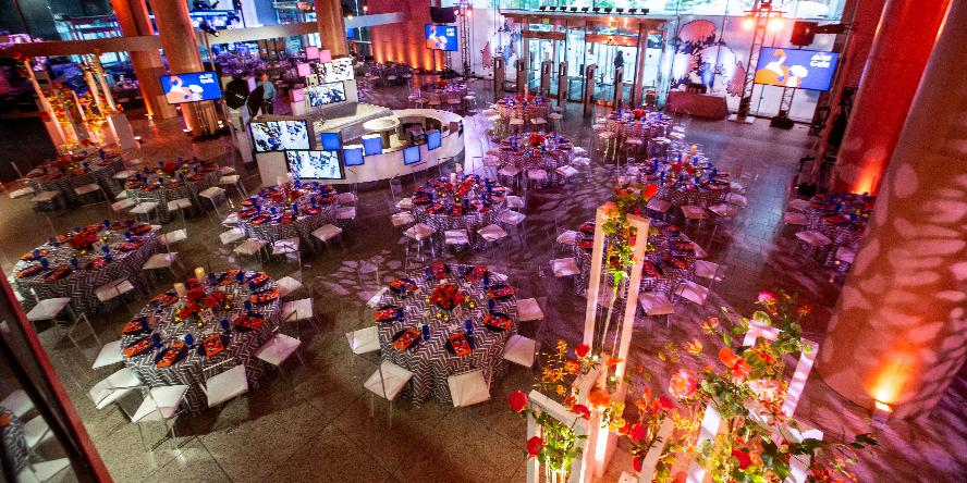 An overview shot of Boylston Hall decorated for the BPL Gala in 2019. There is a stand of large flower arangements, and to the left of it are several large tables with ten seats at each. Each table has a flower centerpiece. There are logos and videos on display in screens that are built into this space. There is orange lighting on the hall.