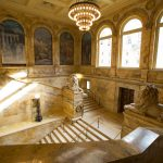 Photo from the left side of the staircase, looking down on the marble steps, and two marble lions. Across the way are a set of the Puvis de Chavannes murals in the gallery.