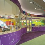 Photo of the exterior of the children's room in the Johnson Building. There is a curved glass wall on the outside, and lighting and fun kid murals, as well as bookcases on the inside