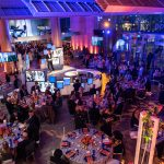 Overhead shot of the BPL Gala with people sitting at tables with blue lighting