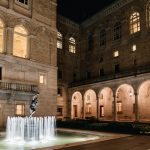 Photo of the McKim Courtyard at night, lit up with lights under the arches, and the fountain running.