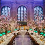 Bates hall set up with white and gold tablecloths, small individual flower arrangements, larger flower arrangements on the tables as well