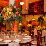 Guastavino Room set up with medium circular tables with tablecloths, cloth napkins, glasses, and a large flower arrangement on each table.