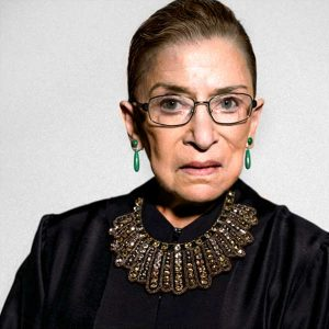 Image of Ruth Bader Ginsburg wearing her dissent jabot. It is gold with lines radiating from the top of the neckline to the bottom