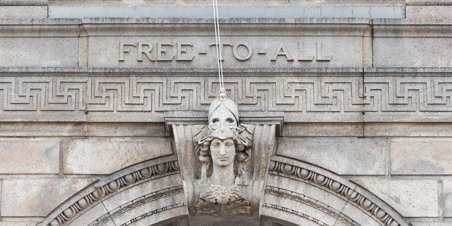 "Exterior of entrance to the McKim Building of the Boston Public Library (Dartmouth Street Entrance). The image shows a bust of Minerva (Roman god of knowledge). Above it, inscribed in stone are the words, ""Free to All"""