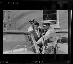 Positive image of a photographic negative showing two police officers placing a man in an automobile.