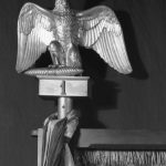 A bronze eagle finial on top of a silk Napeleonic flag