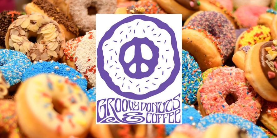 Groovy Donuts logo pictured on a bed of donuts.