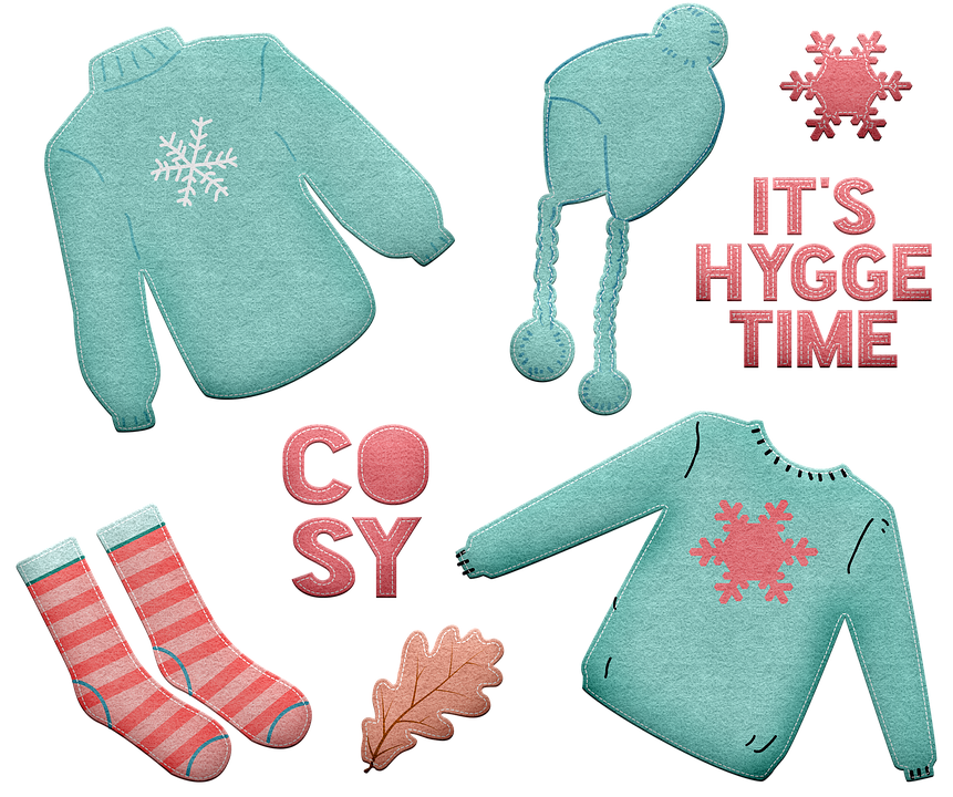 Cozy items like warm socks, sweaters and hats with the text It's Hygge Time