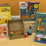 Baby prizes for the 2021 Summer Reading season, including board books, a sculpting kit, and chunky crayons