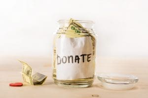 A glass jar labeled Donate with paper bills tucked inside of it