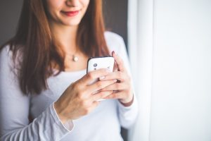 A white woman using a smart phone