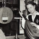 Phyllis Sands examines one of the old musical instruments in the Central Library, November 11, 1946. From the monogrammed jumper and the white shirt with French cuffs that Phyllis is wearing, we know she was a pupil at St. Joseph's Academy.
