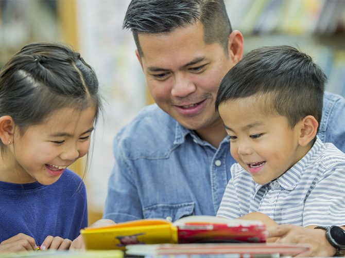 An Asian father and his daughter and son are reading a book at the library. They are sitting at a table and looking at the book, smiling and laughing.
