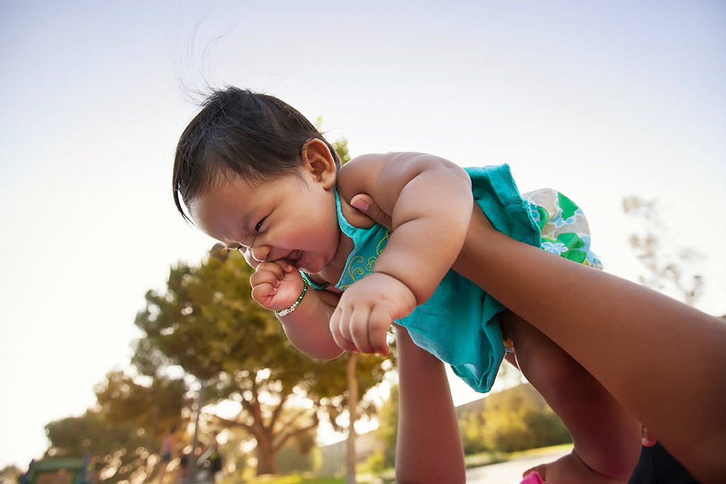 Baby girl being lifted up by mother into the sky, baby looks excited and nervous.