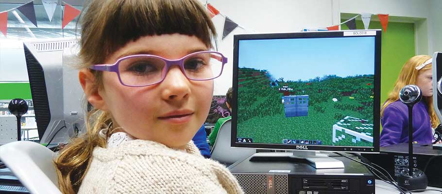Girl at computer playing minecraft