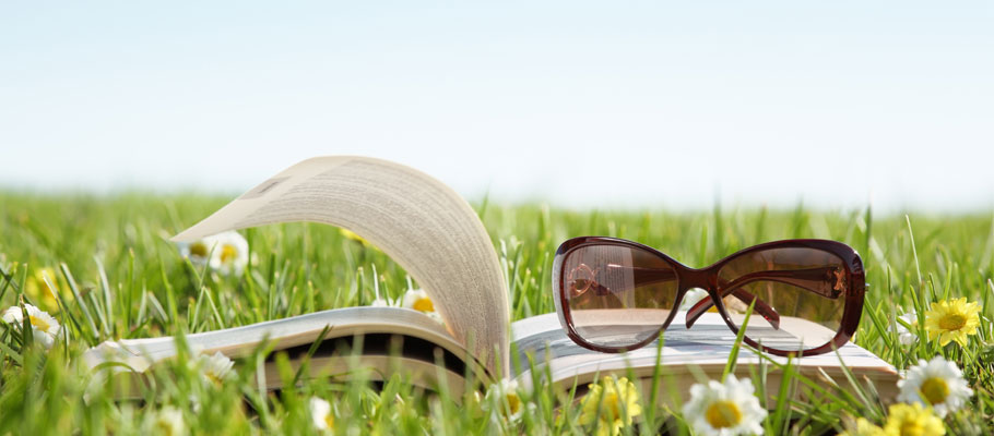 Photo of sunglasses on an open book lying in the grass