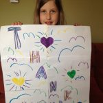 young girl holds up thank you card