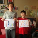 two young boys hold up thank you card