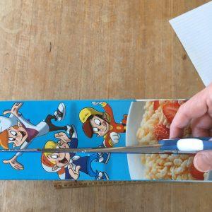 cutting along narrow edge of cereal box