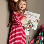 girl holding monkey and me book with monkey toy