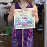 girl dressed as mermaid holding mermaid book