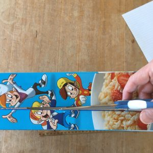 cutting along narrow edge of cereal box