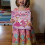 girl dressed as pinkalicious holding pinkalicious book
