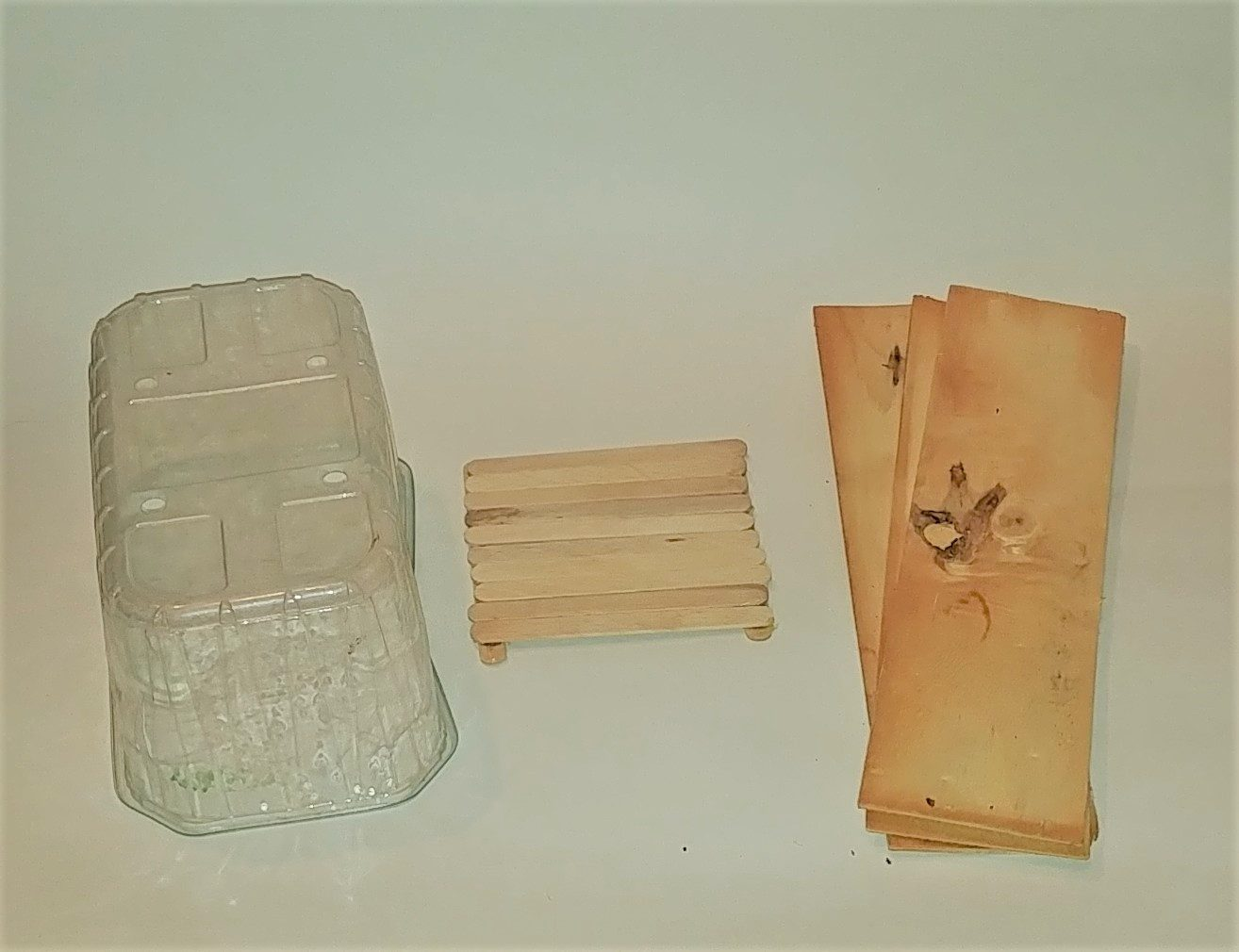 container, popsicle sticks, and wood for fairy house construction