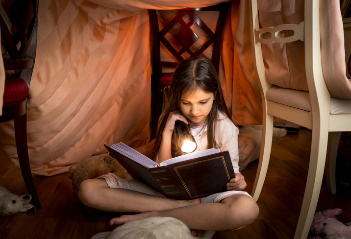 girl under a blanket reading a book